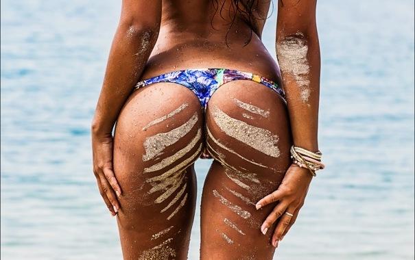 Песок на пляжных женских попках